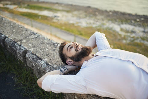 Man with beard lying on a wall at the riverside - ZEDF02539