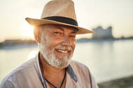 Portrait of a smiling senior man wearing summer hat at the riverside at sunset - ZEDF02548