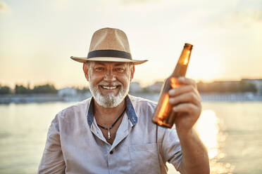 Portrait of a happy senior man drinking a beer at the riverside at sunset - ZEDF02551
