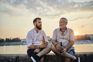 Father and adult son sitting on a wall at the riverside at sunset drinking a beer - ZEDF02554