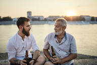 Father and adult son sitting on a wall at the riverside at sunset drinking a beer - ZEDF02557