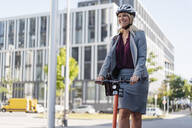 Portrait of happy businesswoman riding electric scooter on the street - DIGF08007
