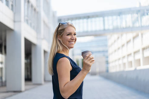 Portrait of smiling blond businesswoman with coffee to go in summer - DIGF08016