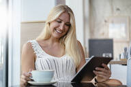 Portrait of smiling blond woman in a cafe using digital tablet - DIGF08019