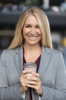 Portrait of smiling blond businesswoman with coffee to go - DIGF08037