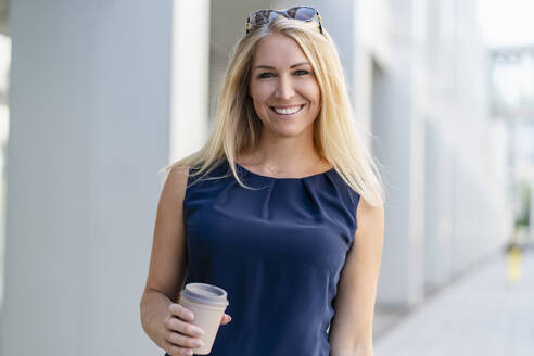 Portrait of smiling blond businesswoman with coffee to go in summer - DIGF08046