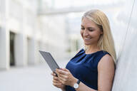 Portrait of smiling blond businesswoman looking at digital tablet - DIGF08049