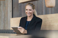 Portrait of smiling blond businesswoman with digital tablet in a coffee shop - DIGF08055
