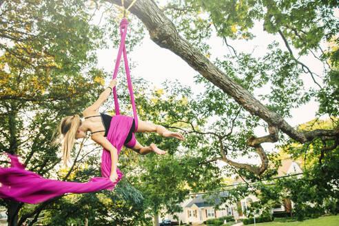Acrobatic Caucasian girl hanging on fabric under tree - BLEF14298