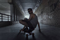 Portrait of young man with longboard in a tunnel - AFVF03788