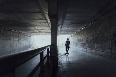 Silhouette of young man longboarding in a tunnel - AFVF03791