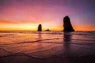 Silhouette of rock formations on Cannon Beach at sunset, Oregon, United States - BLEF14355