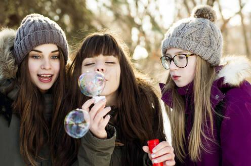 Caucasian girls blowing bubbles outdoors in winter - BLEF14367
