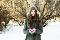 Caucasian girl holding snow in field - BLEF14370