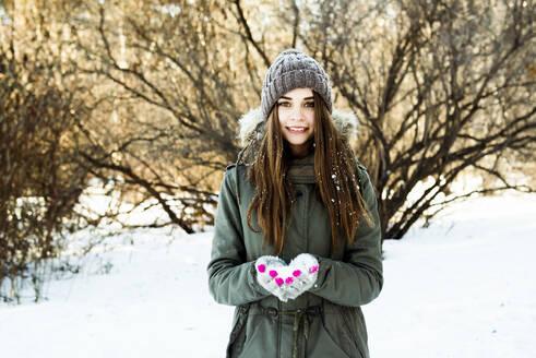 Caucasian girl holding snow in field - BLEF14370