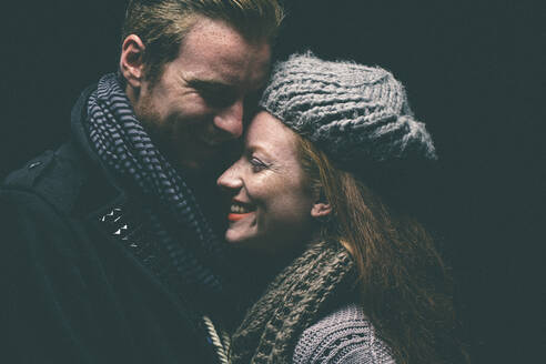 Smiling couple wearing warm clothing hugging - BLEF14412
