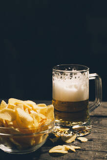 Glass of beer with bowl of potato chips - BLEF14421