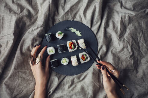 Hands of woman reaching for platter of sushi on bed - BLEF14424