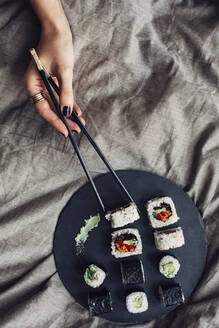 Hands of woman reaching for platter of sushi on bed - BLEF14427