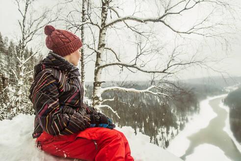 Caucasian hiker sitting on snowy hilltop - BLEF14460