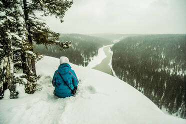 Caucasian hiker sitting on snowy hilltop - BLEF14463