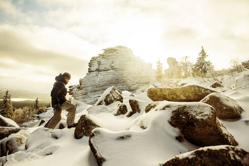 Caucasian hiker climbing snowy rock formations - BLEF14544