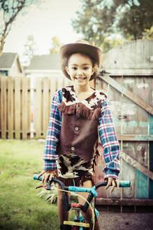 Mixed race girl wearing cowboy costume in backyard - BLEF14628