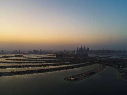 Aerial view of The Palm Jumeirah with Dubai Skyscrapers in the background at sunset, United Arab Emirates. - AAEF01977