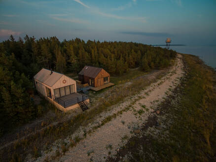 Aerial view of two houses on the beach at sunset - AAEF02002