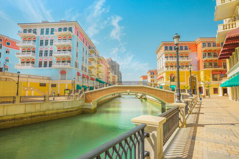 Beautiful Little Venice with canals connected by bridges in Venetian style and colourful houses in picturesque Qanat Quartier, Venice at the Pearl, Doha, Qatar, Middle East - RHPLF00360