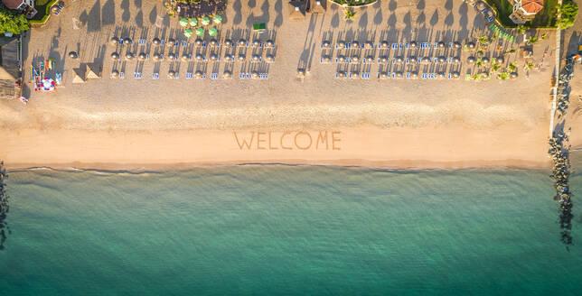 Aerial view of coastline beach, umbrellas and welcome sign in Al Aqah, Dubai - AAEF02257