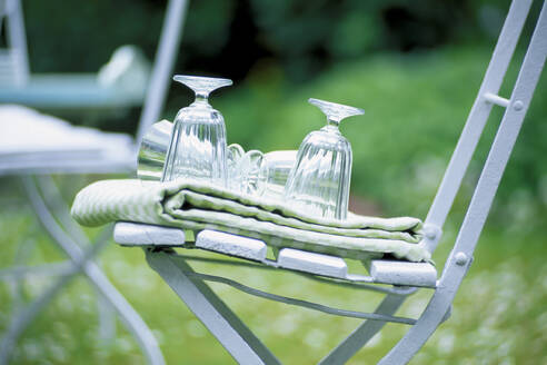 Glasses and tablecloth on wooden chair in backyard - PPXF00229