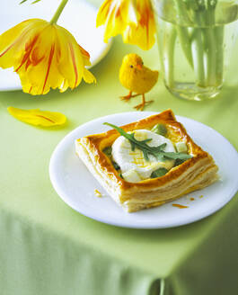 Goat cheese tartlet in plate by flower and decoration on table - PPXF00245