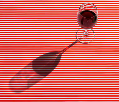 High angle view of red wine served on striped table - KSWF02052