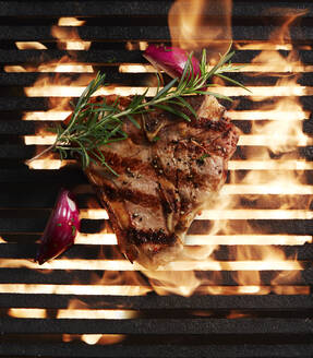 Directly above shot of fresh steak grilling and onion with herb on barbecue - KSWF02061