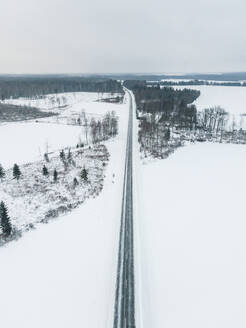 Aerial view of an empty road in the middle of the nordic landscape in winter in Estonia - AAEF02478