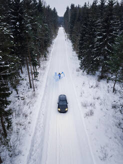 Aerial view of a man lighting a blue smoke grenade on a snowy road in the forest in Estonia - AAEF02487