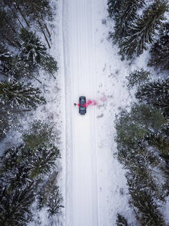 Aerial view of a man lighting a pink smoke grenade on a snowy road in the forest in Estonia - AAEF02490