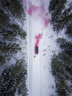 Aerial view of a man lighting a pink smoke grenade on a snowy road in the forest in Estonia - AAEF02493