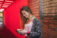 Happy young woman using cell phone in the city - TAMF02082