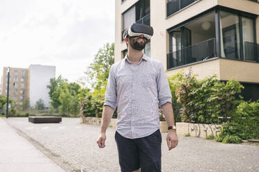 Man wearing Virtual Reality Glasses outdoors - TAMF02100
