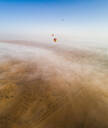Aerial view of a group of hot-air-balloon flying in the clouds of the Murqquab desert in Dubai, UAE - AAEF02885