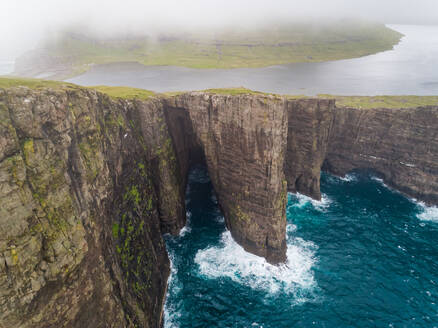 Aerial view of tourists English Slave cliff on North Atlantic sea, Faroe island. - AAEF02957