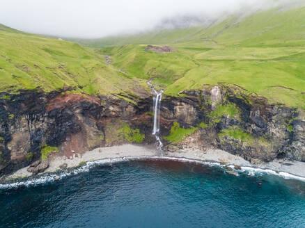 Aerial view of small waterfall ending on North Atlantic sea, Faroe island - AAEF02960