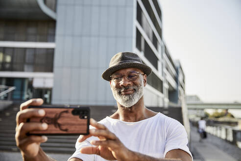 Portrait of smiling mature man with grey beard taking selfies with smartphone - FMKF05883