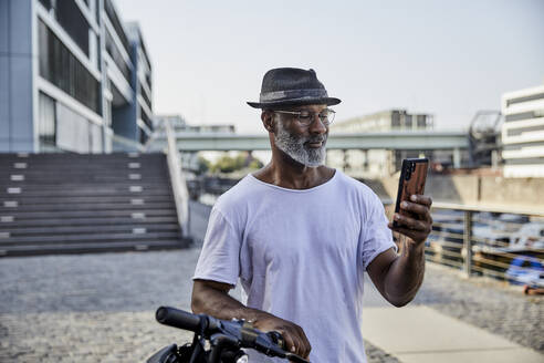 Portrait of smiling mature man with E-Scooter looking at mobile phone - FMKF05886