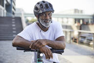 Portrait of smiling mature man wearing cycling helmet leaning on handlebar of Electric Scooter - FMKF05889