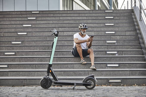 Mature man with E-Scooter sitting on stairs using cell phone - FMKF05892