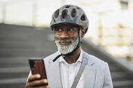 Portrait of smiling mature businessman with smartphone wearing cycling helmet and glasses - FMKF05898