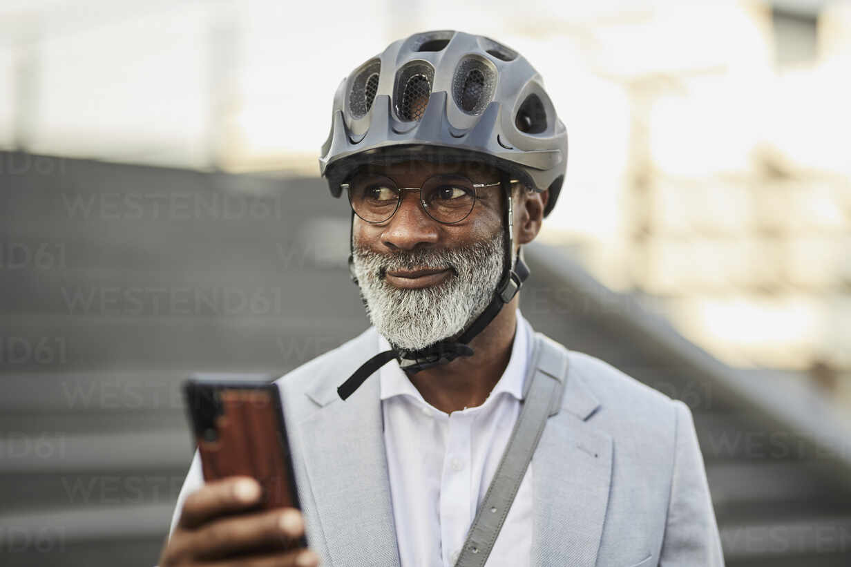 Portrait of smiling mature businessman with smartphone wearing cycling helmet and glasses - FMKF05898 - Jo Kirchherr/Westend61
